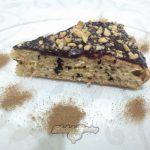 Фото 1. Отрезанный кусочек бисквита с кусочками шоколада.
